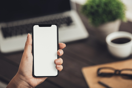 Woman holding new big smartphone with blank screen for mockup, copy space