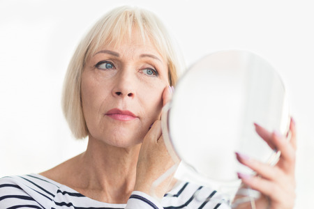 Elderly woman applying face cream, looking at mirror at home
