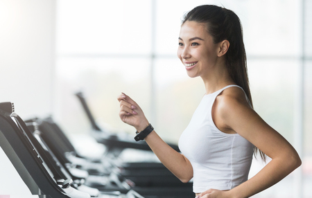 Woman working out, doing cardio exercise in gym, copy space