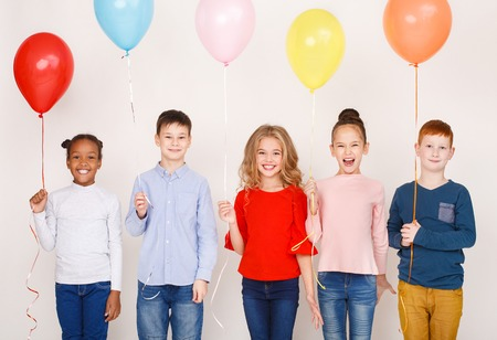 Group of children with colourful balloons over white wall
