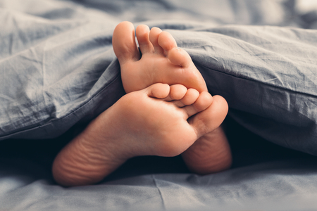 Female beautiful bare feet under gray blanket in bed, closeup