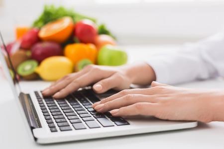 Gezond eten en eten coach concept. Voedingsdeskundige consultatie online, diëtist typebehandeling aan patiënt via internet, kopieer ruimte Stockfoto