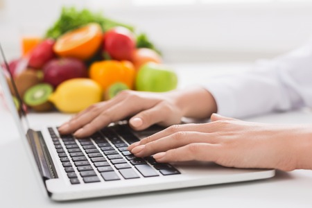 Healthy eating and food coach concept. Nutritionist consultation online, dietitian typing treatment to patient via internet, copy space