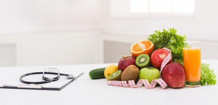 Doctor nutritionists workplace with healthy organic food and stethoscope, panorama, copy space