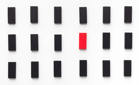Mobbing, bullying and individuality. One red wooden block between black ones, panorama