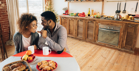 Happy millennial african-american couple enjoying tasty pastry in kitchen, panorama, copy space