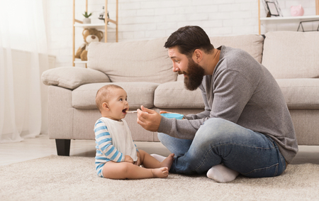 Dad feeding baby son, showing how to open mouth and say Yum, sitting on floor at home, copy space Banco de Imagens