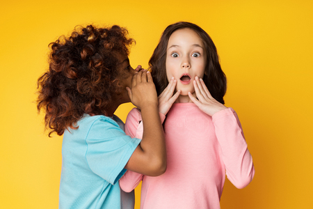 Girl telling secret to her friend, whispering in ear, yellow studio background