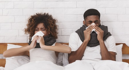 Sick together. Young african-american couple sneezing into paper napkins in bed, panorama Stock Photo