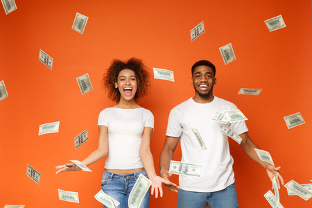 Financial success. Excited young african-american couple standing under money banknotes shower, orange background Zdjęcie Seryjne