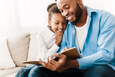 African-american girl and father enjoying reading book together