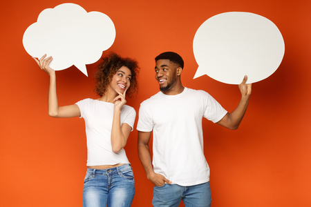 Young african-american couple holding speech bubbles, looking at each other and smiling, flirting on orange background 版權商用圖片