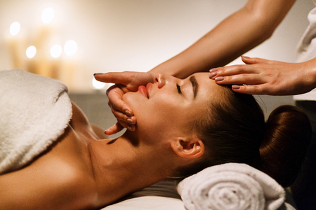 Woman enjoying anti aging facial massage in atmospheric spa, side view Archivio Fotografico