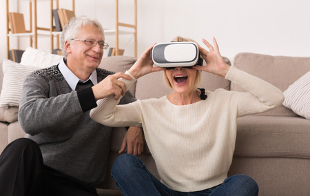 Mature couple using virtual reality headset, watching video in living room Stock Photo