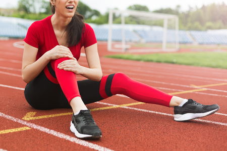 Woman has pain in knee after run at stadium. Sport knee injury concept