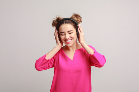 Happy woman listening music in headphones on grey background Stock Photo