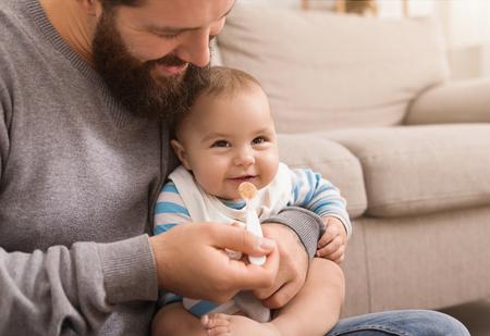 Cute baby eating porridge, having fun with his dad, closeup, copy space Banco de Imagens