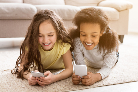 Little friends playing on smartphones or watching videos, lying on floor at home