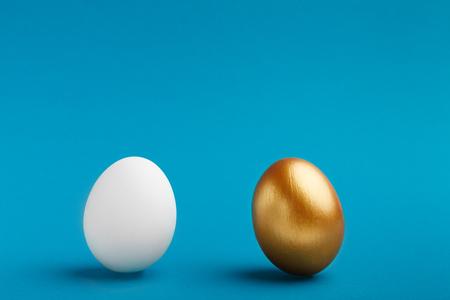 Elita kontra ludzie. Białe i złote jajka na niebieskim tle, kopia przestrzeń Zdjęcie Seryjne