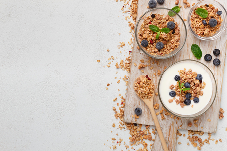 Granola and yogurt in bowls on white background, top view. Recipe of healthy breakfast, mockup, copy space