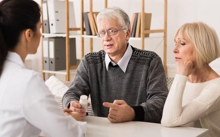 Enfermera explicando medicamentos recetados a la pareja de ancianos en casa