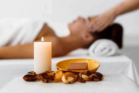 Aroma composition with candle and soap, woman receiving massage on background