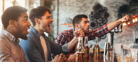 Diverse friends watching football game and drinking beer in bar