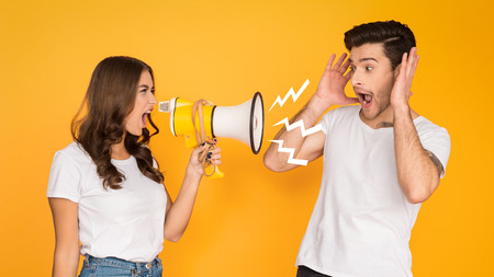 Woman shouting angrily at man with loudspeaker, yellow Stockfoto