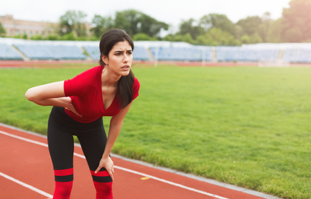 Female runner on running track has side cramps during workout