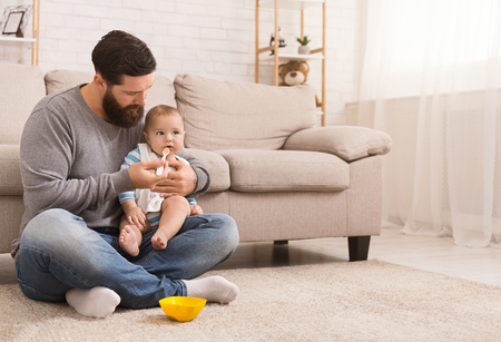 Father takes care of his little son, feeding baby with porridge at home, copy space