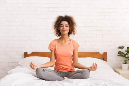 Meditation. Woman sitting in lotus pose on bed in the morning at home Reklamní fotografie