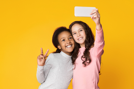 Girls making selfie on smartphone, showing v-sign on shine yellow