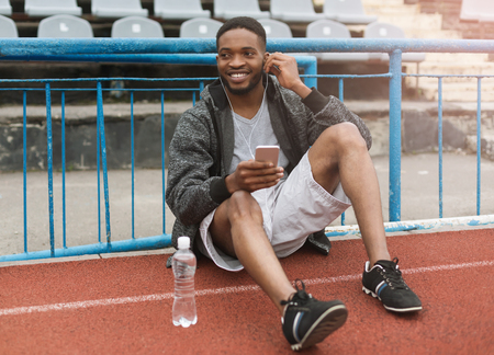 Sporty black man sitting on stadium, relaxing and listening to music with earphones. Relaxed sportsman concept