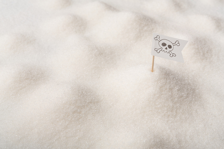 Danger of diabetes. Jolly Roger flag on seamless sea of white sugar, copy space