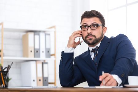 Shocked businessman talking on phone, writing report in office, copy space Standard-Bild