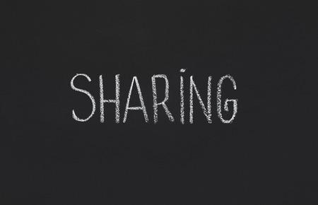 Earnings per Share. Word Sharing written on black chalkboard, copy space Imagens