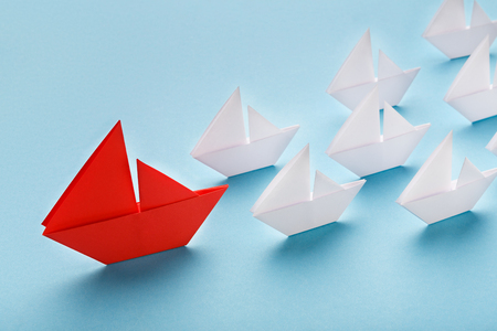 Opinion Leader, influencer concept. One red boat leading small white ships on blue background