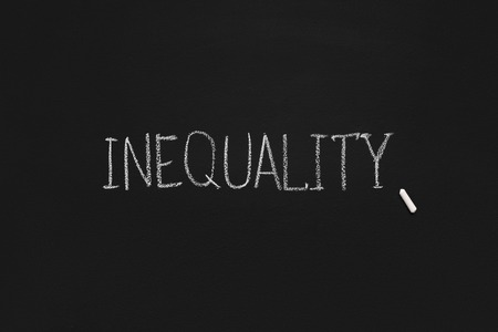 Word Inequality written with chalk on blackboard background, panorama