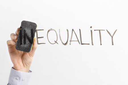 Equality concept. Man cleaning part In in word Inequality written on glass board, copy space