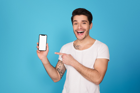Guy pointing on smartphone with blank screen, showing application against blue background Reklamní fotografie