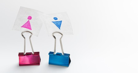 Concept of heterosexual couple who met at work. Pink and blue bulldog clips with gender figures next to each other, panorama, copy space