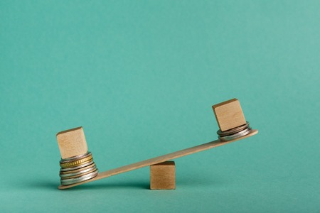 Pay gap and discrimination. Empty wooden cubes on seesaw with different stacks of coins, one outweigh, copy space Stock Photo