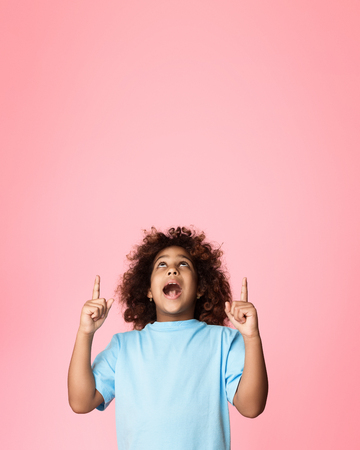 African-american girl pointing fingers up and shouting, pink background, copy space Stock Photo