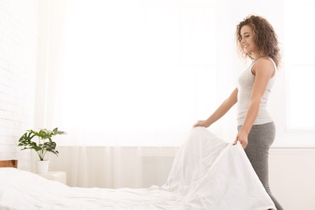 Young woman making bed and organizing room in morning, copy space
