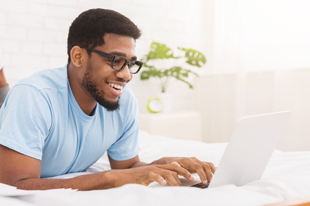 Black man blogger typing on laptop, chatting with followers, enjoying wireless internet in bed, copy space