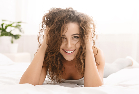 Cheerful woman relaxing in bed, playing with her hair, closeup Stock Photo