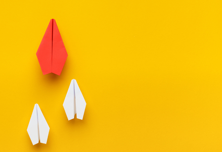 Leadership concept. Red paper plane leading another white ones, showing successful strategy way, yellow background, panorama, copy space
