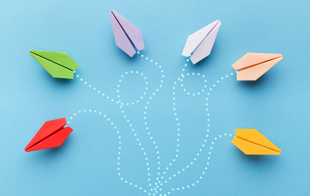 Choose your own way. Colorful paper planes with route trace on blue background, copy space