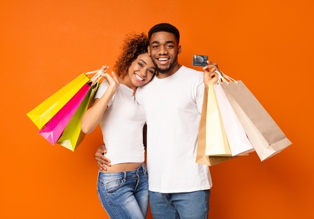 Attractive young african-american couple with shopping bags and credit card on orange background