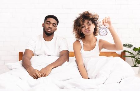 Deberíamos irnos a la cama más temprano. Pareja afroamericana soñolienta sentada en la cama con reloj despertador, no puede despertarse por la mañana, espacio de copia Foto de archivo